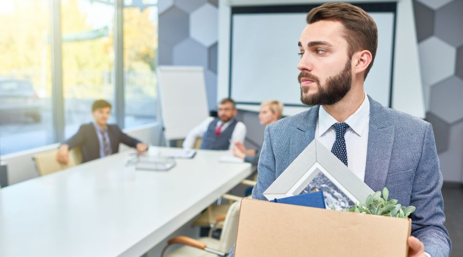 man walking out of conference room holding a box