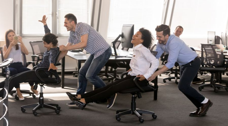employees laughing and holding a chair race