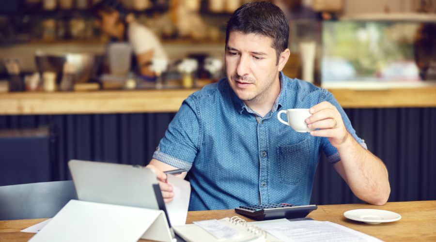 small business owner drinking coffee and calculating how much to pay himself