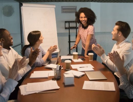 woman giving presentation to coworkers who are clapping