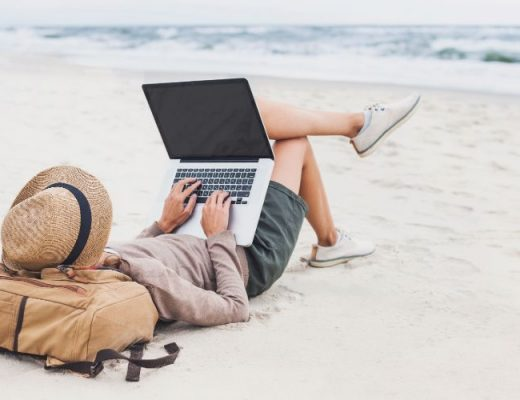 person reviewing time off requests on a laptop while lying on the beach